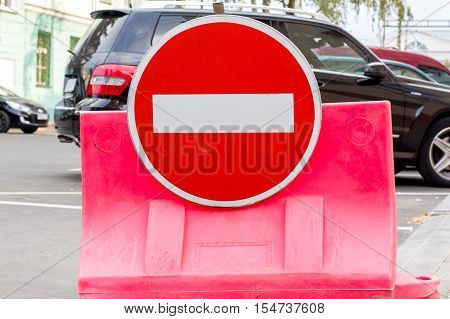 Round prohibitory sign traffic plastic barrier in front of a black car
