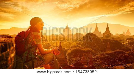 Young traveller enjoying a looking at sunset on Bagan Myanmar Asia. Traveling along Asia active lifestyle concept
