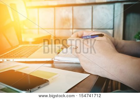 Business Man working at office hand holding pen with use laptop computer smartphone and stock maket document and smartphone on his desk.