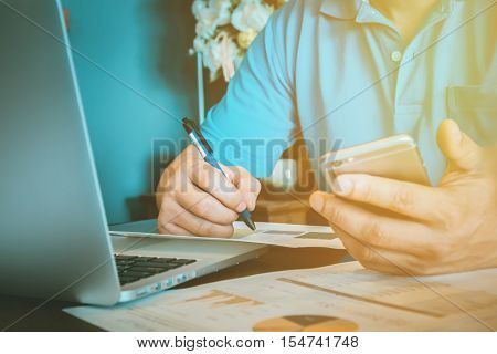 Close up Business Man working at office hand holding pen point stock maket document and use smart phone and laptop on his desk. vintage effect.