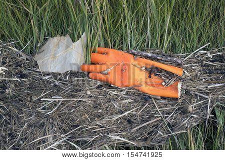 White plastic and orange rubber glove abandoned on the beach on Mando island in Denmark. Danish national park under UNESCO World Heritage.