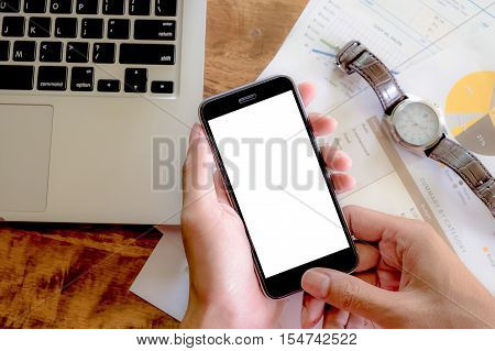 hand holding smart phone with coffee on wood desk. Smart phone with blank screen and can be add your texts or others on smart phone.Smart phone concept.
