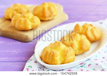 Delicious sweet eclairs or profiteroles with cream. Home made eclairs filled with butter cream on a plate and wooden cutting board. Closeup