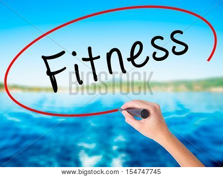 Woman Hand Writing Fitness With A Marker Over Transparent Board