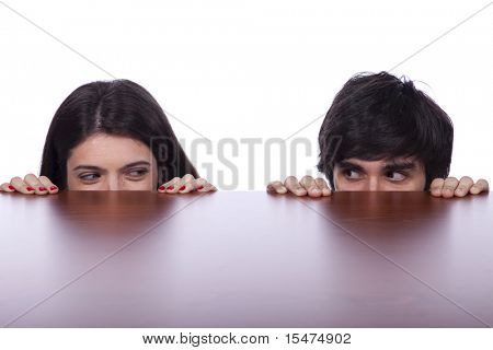 two business person hiding and peeking behind the office desk