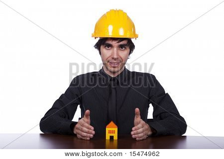 young construction engineer protecting a small yellow house