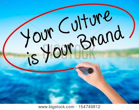 Woman Hand Writing Your Culture Is Your Brand With A Marker Over Transparent Board