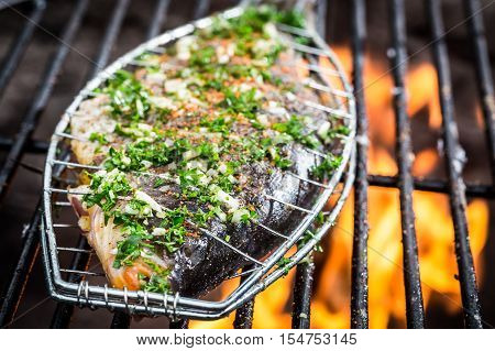 Grilled fish with spices on hot grill with fire