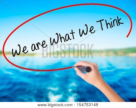 Woman Hand Writing We Are What We Think With A Marker Over Transparent Board