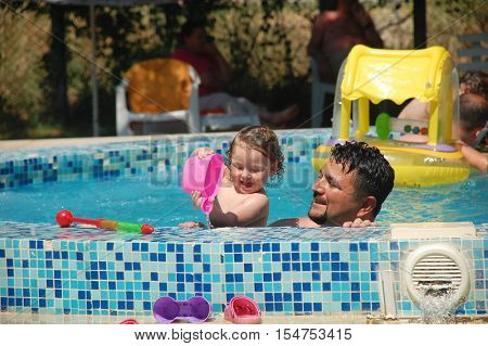 Dad and cute little girl. They're having fun in the pool.