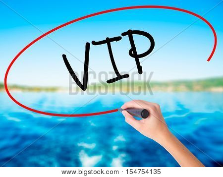 Woman Hand Writing  Vip With A Marker Over Transparent Board