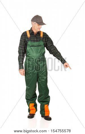 Mature gardener in uniform pointing down