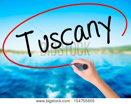 Woman Hand Writing Tuscany With A Marker Over Transparent Board.