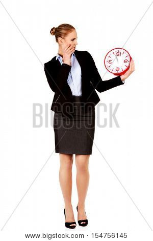 Shocked business woman holding office clock