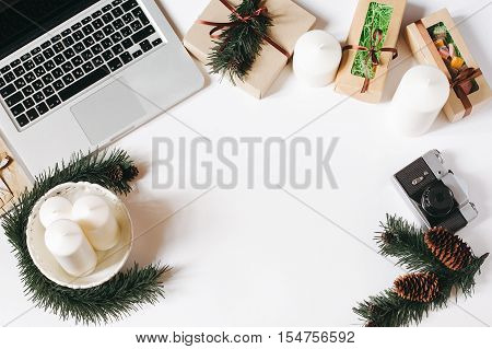 Workspace in Christmas style with laptop, white candles, decorative gifts and spruce branches with cones and vintage film camera on white background. Freelance and work on holidays concept. Top view, Flat lay