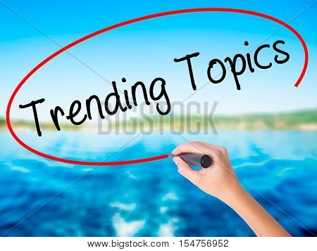 Woman Hand Writing Trending Topics With A Marker Over Transparent Board