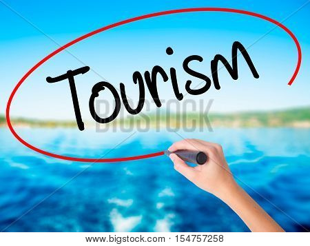 Woman Hand Writing Tourism With A Marker Over Transparent Board.