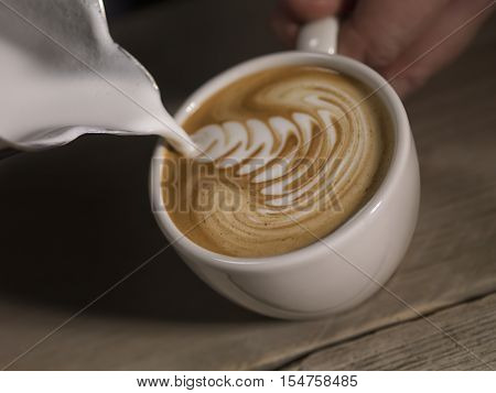 Cappucino in coffe cup with a melk can