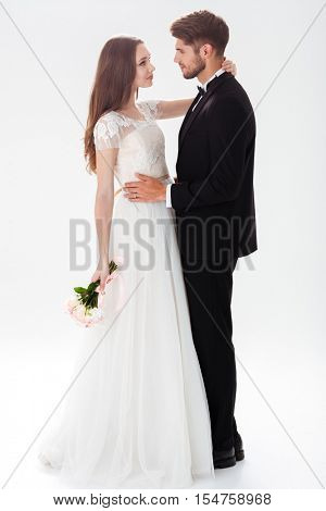 Full-length portrait of pretty newlyweds with bouquet. isolated white background