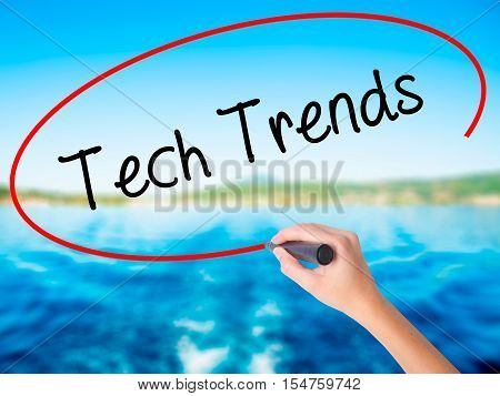 Woman Hand Writing Tech Trends With A Marker Over Transparent Board