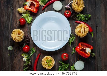 Ingredients for cooking spagetti cherry tomatoes pepper around a white plate place text frame on wooden rustic background top view.
