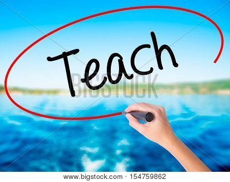 Woman Hand Writing Teach With A Marker Over Transparent Board.