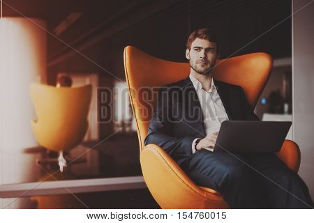 Young serious successful man entrepreneur in formal business suite with a beard sitting on orange armchair with laptop in luxury office interior preparing to business meeting