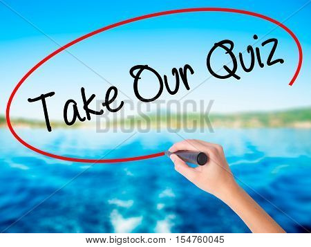 Woman Hand Writing Take Our Quiz With A Marker Over Transparent Board