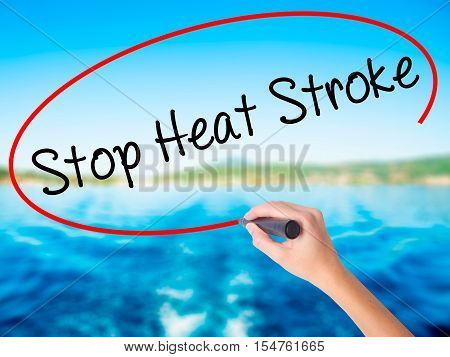 Woman Hand Writing Stop Heat Stroke With A Marker Over Transparent Board.