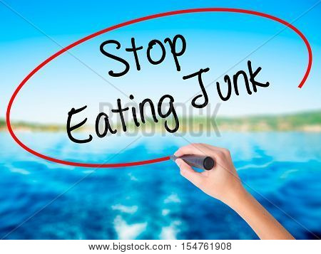 Woman Hand Writing Stop Eating Junk With A Marker Over Transparent Board.