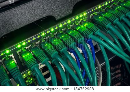 Close up of green and blue network cables connected to black switch patch panel glowing in the dark