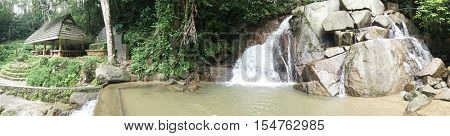 Panaoramic view photo of small mountain waterfall on the rocks and cozy alcove foe relax in the tropical forest