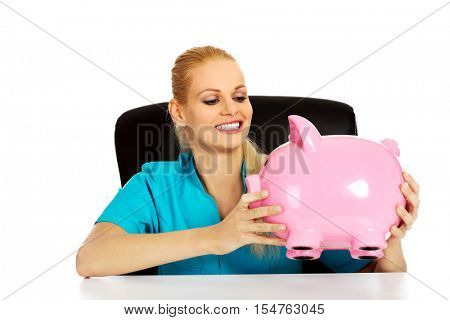 Young female doctor or nurse sitting behind the desk and holding piggybank