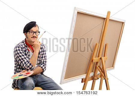 Painter posing next to a canvas and contemplating isolated on white background
