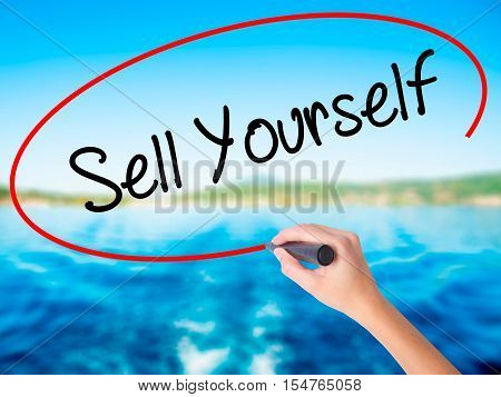 Woman Hand Writing Sell Yourself With A Marker Over Transparent Board
