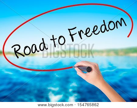 Woman Hand Writing Road To Freedom With A Marker Over Transparent Board.