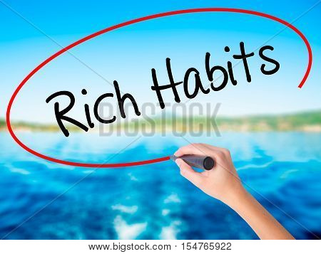 Woman Hand Writing Rich Habits With A Marker Over Transparent Board
