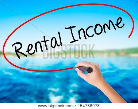 Woman Hand Writing Rental Income With A Marker Over Transparent Board.
