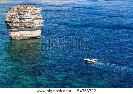 A speedboat heading towards a tall rock in the middle of a clear blue sea