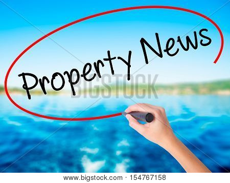 Woman Hand Writing Property News With A Marker Over Transparent Board.