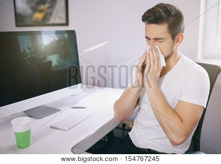 Side view of the patient's employer. sneezing into a tissue in an office near the window in the computer. Freelancer designer with a cold