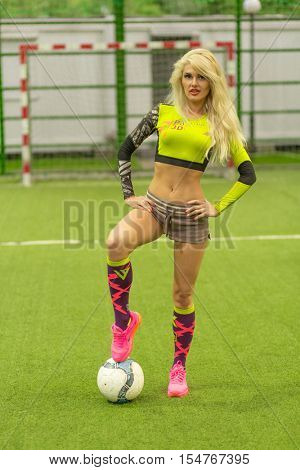 MOSCOW - JUL 16, 2015: Blonde woman (with model release) with ball on soccer field against background of gate