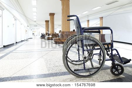 An empty wheelchair in a light hospital corridor with some blurred figures of patients.