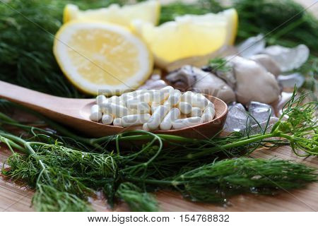 The zinc supplementary white capsule with fresh oyster on block wood