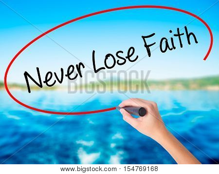 Woman Hand Writing Never Lose Faith With A Marker Over Transparent Board