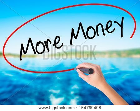Woman Hand Writing More Money With A Marker Over Transparent Board