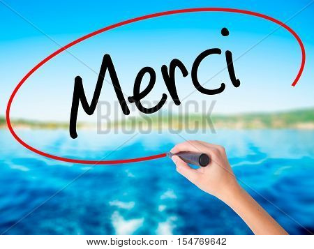 Woman Hand Writing Merci  (thank You In French) With A Marker Over Transparent Board.