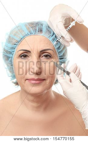 Doctor hands with hyaluronic acid injection and scalpel near senior woman face
