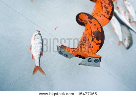 Red Fishing auger on an ice