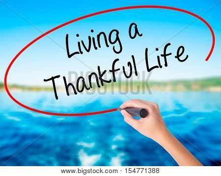 Woman Hand Writing Living A Thankful Life With A Marker Over Transparent Board